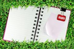 La página en blanco del cuaderno en hierba y la carpeta acortan Imagen de archivo