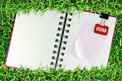 La página en blanco del cuaderno en hierba y la carpeta acortan Fotografía de archivo