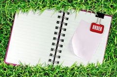 La página en blanco del cuaderno en hierba y la carpeta acortan Fotografía de archivo libre de regalías