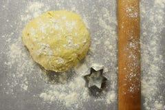La pâte crue avec la goupille en bois et l'étoile forment pour faire sur cuire au four la table avec de la farine Fond à cuire et Image stock