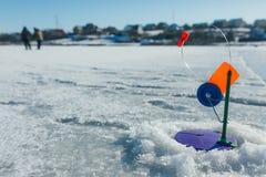 La pêche d'hiver, canne à pêche se tient sur le trou attendant les poissons Photo stock