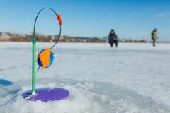 La pêche d'hiver, canne à pêche se tient sur le trou attendant les poissons Photos stock