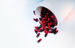 La píldora roja, negra de las cápsulas se derramó hacia fuera del envase plástico blanco de la botella Resistencia a los medicame foto de archivo libre de regalías