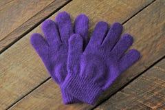 La púrpura embroma guantes del invierno en un fondo de madera aislado Fotos de archivo libres de regalías
