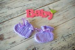 La púrpura hizo a ganchillo calcetines del bebé con la inscripción del bebé en un fondo de madera Foto de archivo libre de regalías