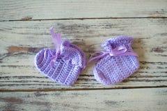 La púrpura hizo a ganchillo calcetines del bebé en un fondo de madera Fotos de archivo libres de regalías