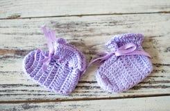 La púrpura hizo a ganchillo calcetines del bebé en un fondo de madera Imagen de archivo libre de regalías