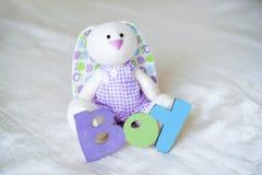 La púrpura hizo punto calcetines del bebé con una inscripción de un niño y de una liebre del juguete Imagen de archivo libre de regalías