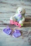 La púrpura hizo punto calcetines del bebé con una inscripción de un niño y de una liebre del juguete en un fondo de madera Imagenes de archivo