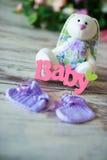 La púrpura hizo punto calcetines del bebé con una inscripción de un niño y de una liebre del juguete en un fondo de madera Fotografía de archivo libre de regalías