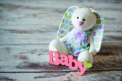 La púrpura hizo punto calcetines del bebé con una inscripción de un niño y de una liebre del juguete en un fondo de madera Fotografía de archivo