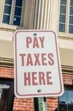 La paga tassa qui il segno Immagine Stock