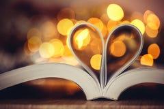 La page de livre décorent à la forme de coeur avec le lig de bokeh de célébration Image stock