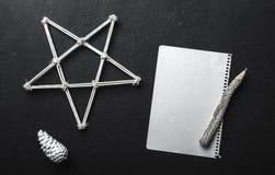 La page du papier blanche sur le fond noir avec un cône de crayon, d'étoile et de sapin Concept de maquette de Noël Image libre de droits