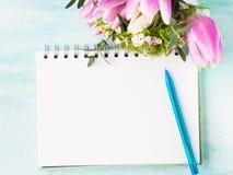 La page vide de carnet avec du café bleu de stylo et de tasse fleurit Photos stock