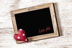 La pagina del giorno del ` s del biglietto di S. Valentino della st ed il cuore casalingo su una struttura di legno bianca imbarc Immagine Stock
