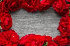 La pagina fatta delle rose rosse fiorisce sulla tavola di legno rustica Immagine Stock