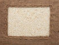 La pagina fatta di tela da imballaggio con la linea si trova sui grani del riso Fotografia Stock