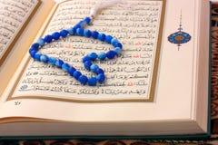 La pagina santa di Koran con il rosario blu Fotografie Stock Libere da Diritti