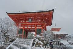 La pagoda rossa al tempio di Kiyomizu-dera con l'albero ha riguardato il fondo bianco della neve Fotografie Stock