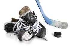 La paire d'hockey patine avec le bâton de hockey et le galet Photographie stock libre de droits