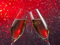 La paire de cannelures de champagne avec de l'or bouillonne sur le fond clair rouge et violet de bokeh Photos stock