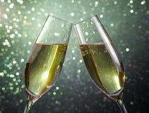 La paire de cannelures de champagne avec de l'or bouillonne sur le fond de bokeh de feu vert Image stock
