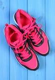 La paire de chaussures roses de sport sur le bleu embarque le fond Photos stock