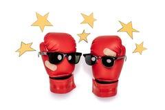 La paire de gants de boxe rouges dans des lunettes de soleil faisant la composition souriante avec le jaune se tient le premier r Photographie stock libre de droits