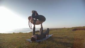 La paire de yoga sur la montagne, acrobate de femme avec des tresses équilibre dans des mains de son associé masculin au soleil s clips vidéos