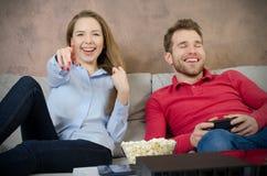 La paire passe le temps gratuit jouant des jeux vidéo Photo stock