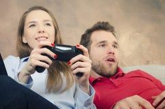 La paire passe le temps gratuit jouant des jeux vidéo Photographie stock