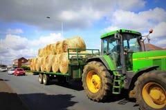 La paja embala el tractor en el camino Reino Unido del campo Imagen de archivo