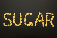 La palabra 'azúcar 'hizo de los copos de maíz en un fondo negro imágenes de archivo libres de regalías