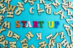 La palabra 'empieza para arriba 'se presenta de letras multicoloras en un fondo azul imágenes de archivo libres de regalías