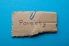 La palabra 'pobreza 'escrita en la cartulina, aislada en un fondo azul, concepto foto de archivo libre de regalías