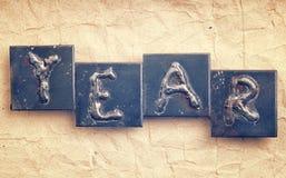 La palabra AÑO hecho de letras del metal Fotos de archivo libres de regalías