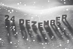 La palabra blanca 24 Dezember significa el 24 de diciembre en la nieve, copos de nieve Fotografía de archivo