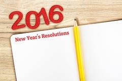 La palabra de las resoluciones del Año Nuevo en el cuaderno pone en la tabla de madera, Templa Fotografía de archivo libre de regalías
