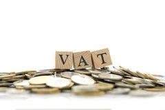 La palabra de madera IVA se pone en una pila de monedas el usar como concepto del negocio del fondo y concepto de las finanzas co fotos de archivo