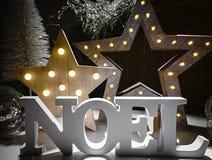La palabra de Noel hecha de letras de madera en un fondo iluminó ingenio Foto de archivo libre de regalías