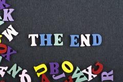 La palabra del FINAL en el fondo negro compuesto de letras de madera del ABC del bloque colorido del alfabeto, espacio del tabler Imágenes de archivo libres de regalías