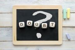 La palabra DUDA y el signo de interrogación escrito en una pizarra Imagen de archivo libre de regalías