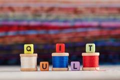 La palabra EDREDÓN se compone de los cubos de imitación de la joyería foto de archivo libre de regalías