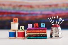 La palabra EDREDÓN se compone de los cubos de imitación de la joyería rodeó los accesorios de costura fotografía de archivo libre de regalías