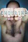 La palabra el AGUANTAR escrito en los puños de un hombre Foto de archivo libre de regalías