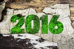 La palabra 2016 escrita en el tipo oxidado de la prensa de copiar del metal que se sienta en un fondo de madera de la repisa Foto de archivo libre de regalías