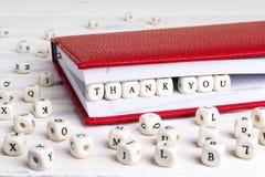 La palabra le agradece escrito en bloques de madera en cuaderno rojo en blanco Imagenes de archivo