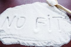 La palabra NINGUNA FIT escrita en un azúcar cubierto y una cuchara de madera en la tabla Fotografía de archivo