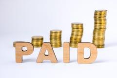 La palabra pagada de letras tridimensionales está en primero plano con las columnas del crecimiento de monedas en fondo borroso C Imagenes de archivo